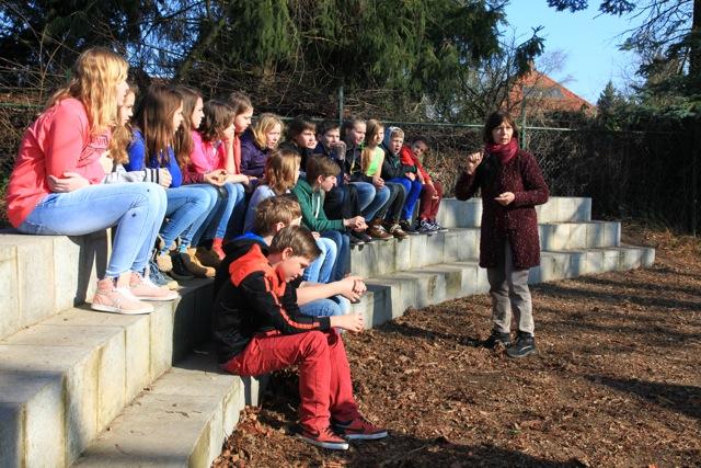 Maria Haanappel van Vereniging Bomenbelang (en lange tijd verbonden aan de Dorpsschool in Vorden) legt de leerlingen van groep 8 uit wat voor groen geplant gaat worden op het schoolplein. Ze deed dat op het pleintje achter de school dat haar naam draagt (foto's: Hans Thijssen).